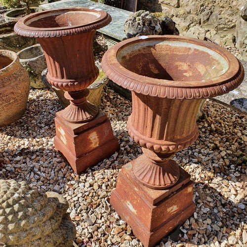 9 - A pair of cast metal campagna form garden urns, on square bases, 69 cm high