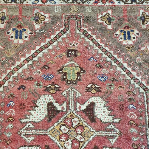 292 - A Persian red ground rug, main cream border, centre with stepped medallions and stylised bird forms,...