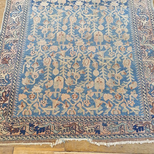 293 - A Persian tribal blue ground rug, with main red border, centered with repeated foliate forms, 192 x ...