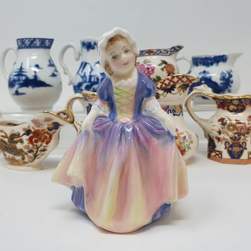518 - A Royal Doulton figure Dinky Do, HN1678, seven modern Royal Worcester blue and white cream jugs and ...