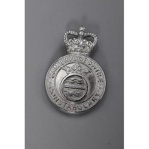 28 - Cambridgeshire Constabulary Helmet Plate plus a Cap Badge...