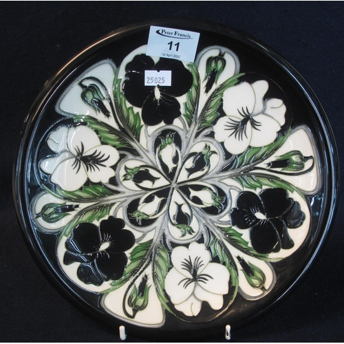 11 - Modern Moorcroft art pottery tube lined cabinet plate or charger, overall on a black ground decorate...
