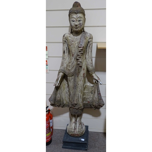 11 - A full size Oriental carved and painted wood floor standing Buddha, with red lacquer headdress, carv...