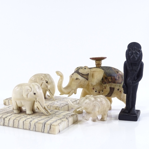 24 - A small group of Indian carved ivory elephant figures, circa 1900, including one with gilded decorat...