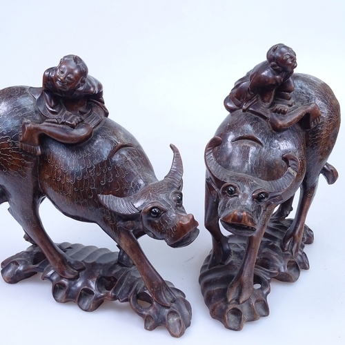 27 - A pair of Oriental carved wood water buffalo with riders, with silver inlay decoration, height 23.5c...