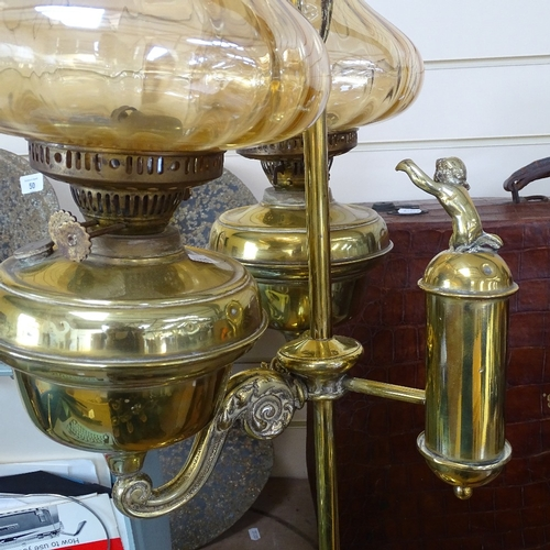 51 - A twin-branch brass oil lamp with lustre shades, height 70cm overall...
