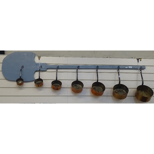 42 - A set of 7 graduated copper pans and pan rack...