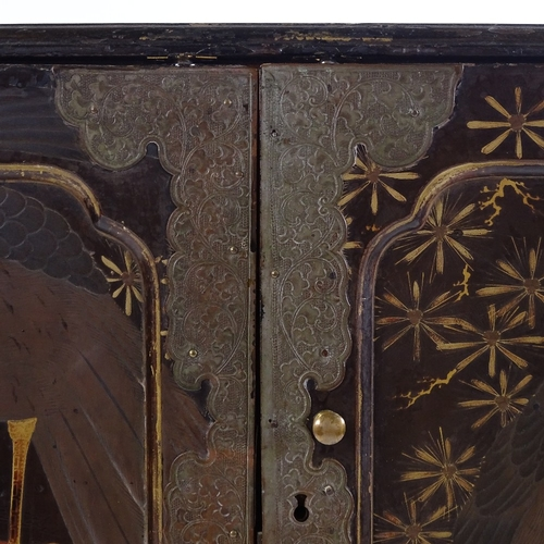 3 - A Japanese Meiji period gilded and lacquered table cabinet with eagle decorated panelled doors, encl...