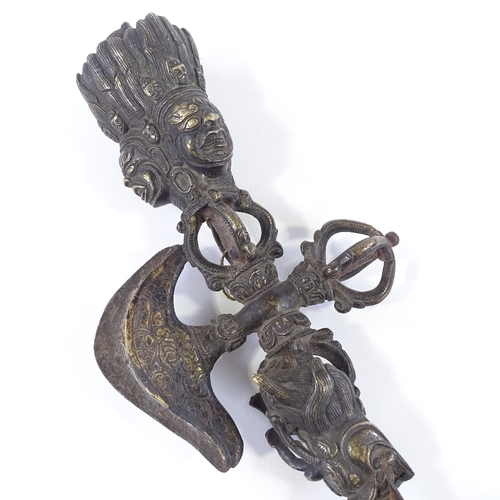 27 - A 19th century Tibetan bronze Thurba, with relief-cast mask decorated handle, length 29cm...