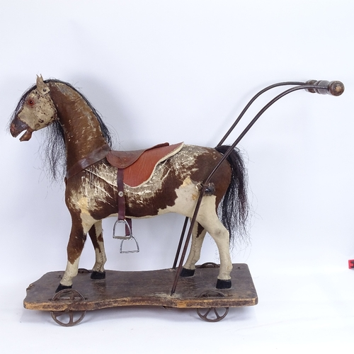 28 - An antique German child's push-along horse toy, pony-skin covered with horse hair mane and tail, on ...
