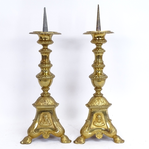 56 - A pair of cast-brass pricket candlesticks, relief embossed religious portraits and scenes, overall h...