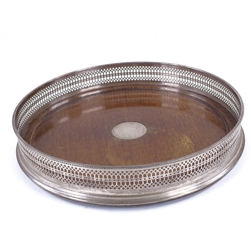 104 - A circular mahogany and silver drinks tray, with pierced gallery, London 1973, diameter 26cm...