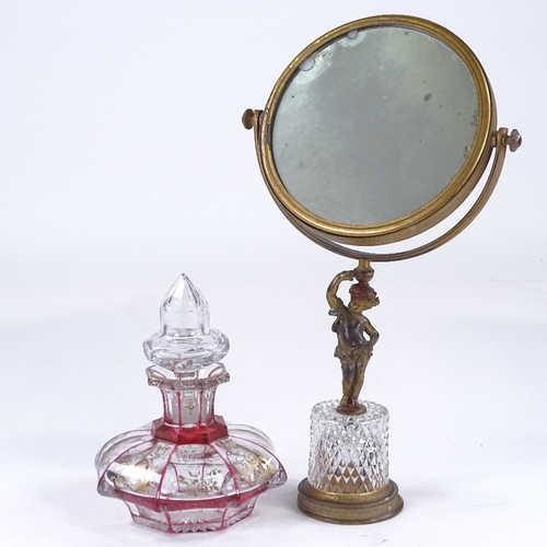 152 - A gilt-bronze and cut-glass shaving mirror, with Classical cherub support, and a cranberry overlay c...