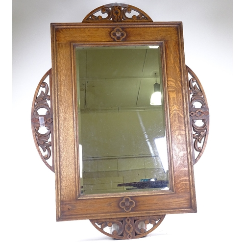 227 - An early 20th century oak-framed wall mirror, with carved and pierced mounts, overall dimensions 98c...