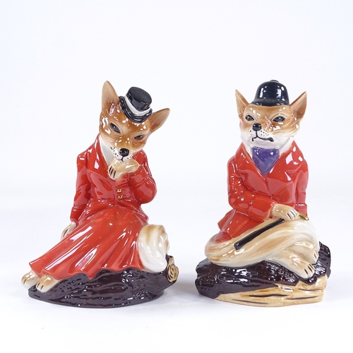 23 - A pair of Cooper Craft Staffordshire China hunting foxes in red coats, height 19cm...
