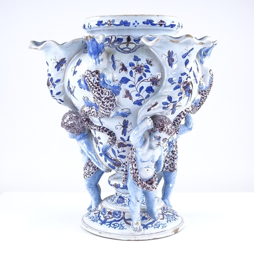 315 - A Delft tin glazed pottery vase, supported by Classical figures, with hand painted decoration, heigh...