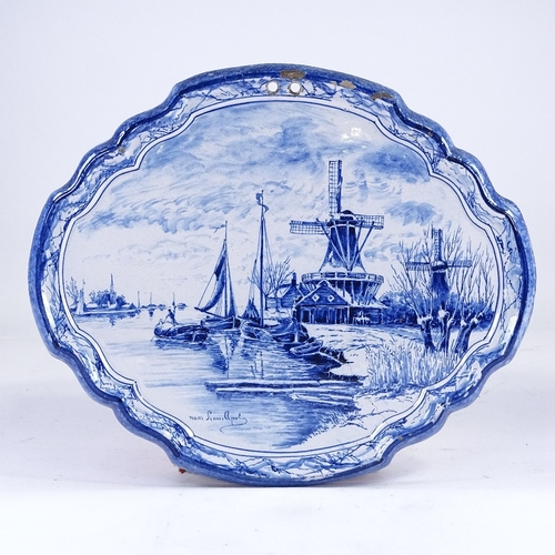 317 - A Delft blue and white pottery wall plaque, with painted canal scene, 39cm across...