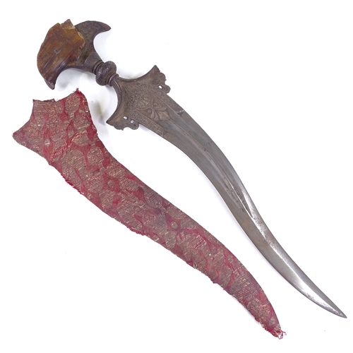 36 - A Middle Eastern Kris dagger, 18th or 19th century, horn handle with floral engraved steel mount, ri...