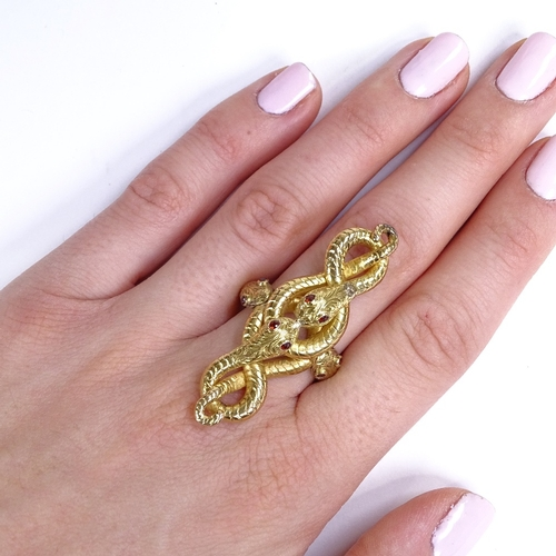 520 - A large unmarked high carat gold entwined snake finger ring, serpents set with garnet eyes with engr...
