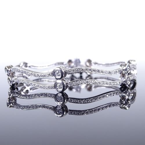 541 - A modern platinum diamond set articulated double-row bracelet, total diamond content approx 2ct, bra...