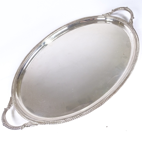 586 - A large Elizabeth II oval silver 2-handled tea tray, gadrooned rim with scrolled acanthus leaf handl...