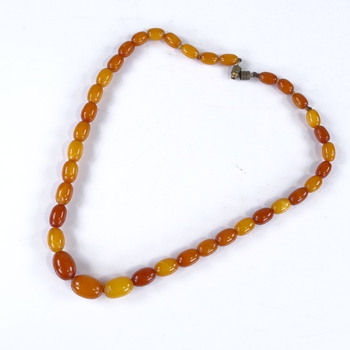 599 - A graduated string of butterscotch amber beads, and a barrel-shaped amber? pendant, largest bead len...