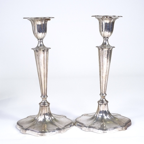 677 - A pair of George V silver table candlesticks, shaped oval form with tapered stick, reeded border and...