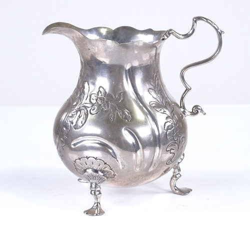 686 - An 18th century Danish silver baluster cream jug, relief embossed and engraved floral decoration, wi...
