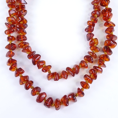 702 - A graduated string of amber beads, individually knotted, necklace length 72cm, 26.8g...