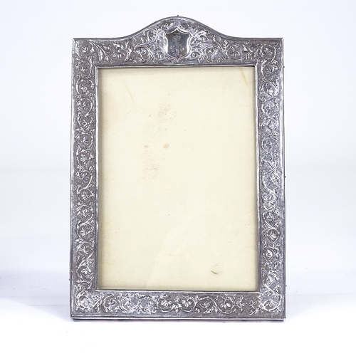 733 - An early 20th century Eastern unmarked silver-fronted rectangular strut photo frame, relief embossed...