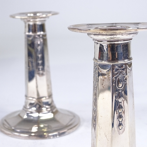 752 - A pair of George V silver squat candlesticks, tapered octagonal form with Adams style decoration, by...