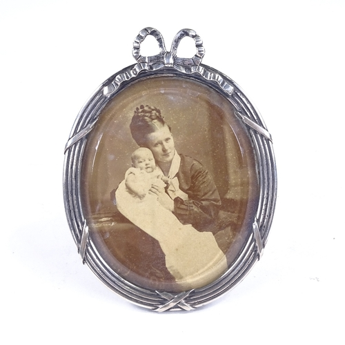 791 - An Art Nouveau Danish oval silver-fronted photo frame, bow decoration with stand, hanging loop and p...