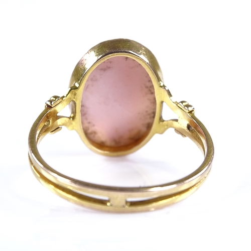862 - An unmarked gold relief carved pink coral cameo panel ring, setting height 16mm, size Q, 2.8g...