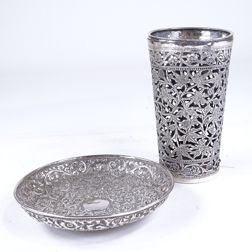 876 - An Indian unmarked white metal dish, and a similar cocktail shaker case, all-over relief and engrave...