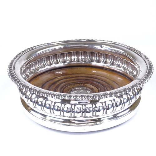580 - A George III silver wine bottle coaster, turned oak base plate with engraved armorial centre disc, b...
