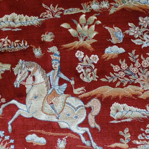 357 - A finely woven Middle Eastern red ground silk rug, depicting hunting scenes...