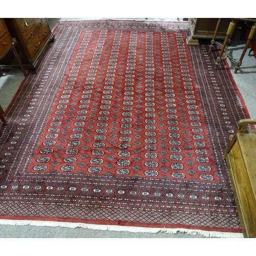 359 - A large Persian handmade red ground geometric design wool rug...