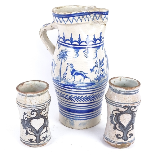 17 - A large Spanish blue and white glazed pottery water flagon, and a pair of Dutch pottery beakers, lar...