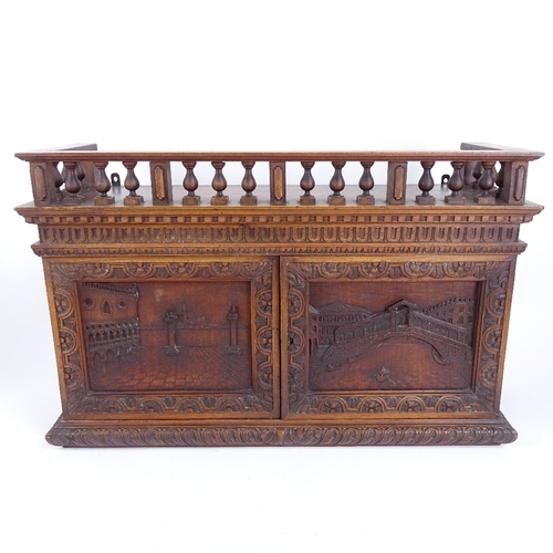 18 - A Grand Tour style carved mahogany wall-hanging cabinet, with Venetian scene carved panel doors, wit...