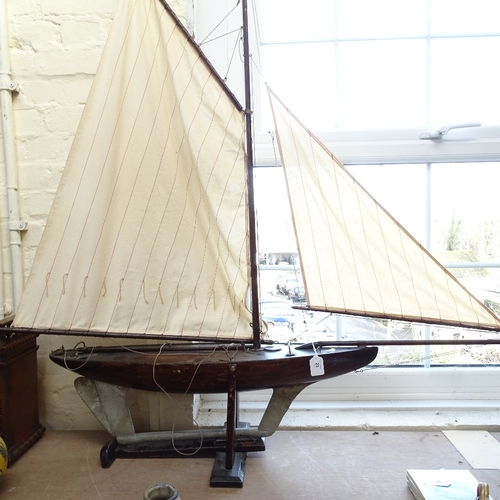 23 - A large 19th century wooden hulled model pond yacht, with masts and rigging, hull length 82cm, on wo...