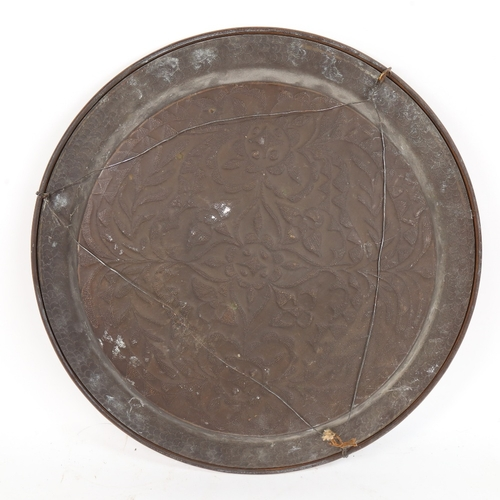 39 - A large brass charger, relief embossed floral decoration, diameter 46cm