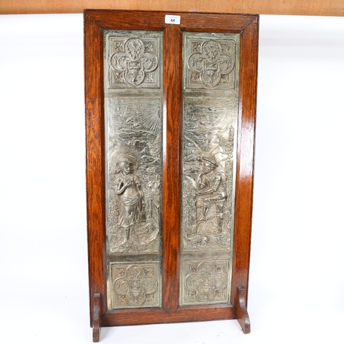 44 - A large Victorian 2-section cast-iron fire screen, relief figural decoration with oak frame, registe...