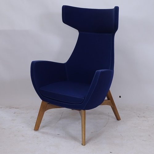 A contemporary designer wing lounge chair upholstered in blue, on splayed legs