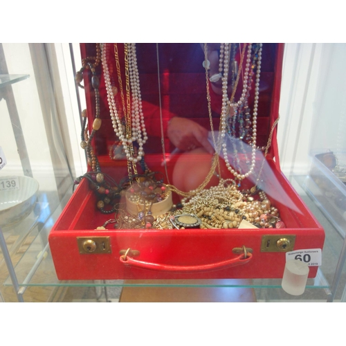 60 - Red jewellery box containing a large amount of beads and necklaces...