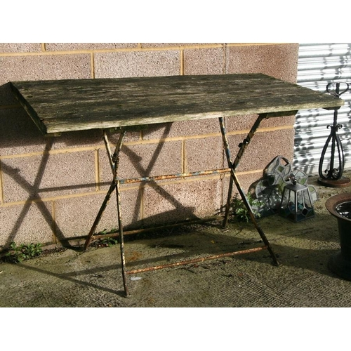 20 - A French wood and wrought iron garden table, 125cms (49ins) wide; together with four matching chairs...