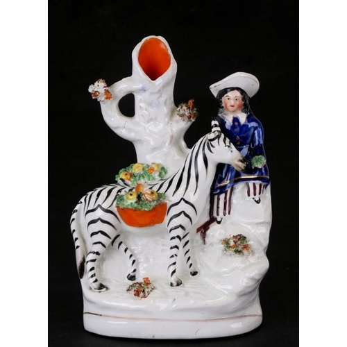 43 - A 19th century Staffordshire spill vase depicting a figure with a zebra, 16cms (6.25ins) high....