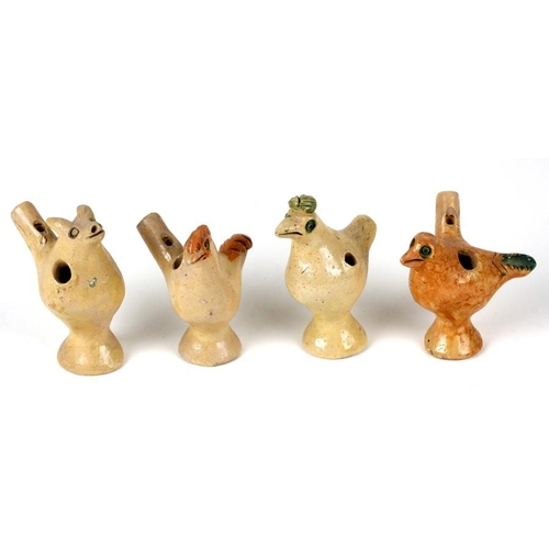 46 - A group of four pottery whistles, three in the form of birds and one in the form of a pig, the large...