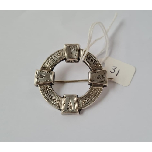 31 - A silver circular Victorian brooch with engraved decoration