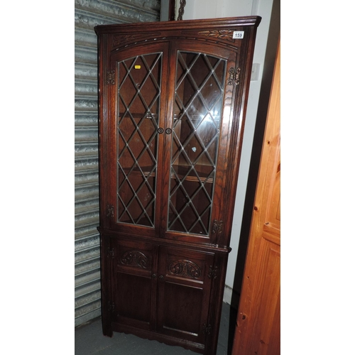 159 - Old Charm-style glazed corner cupboard with carved detail...