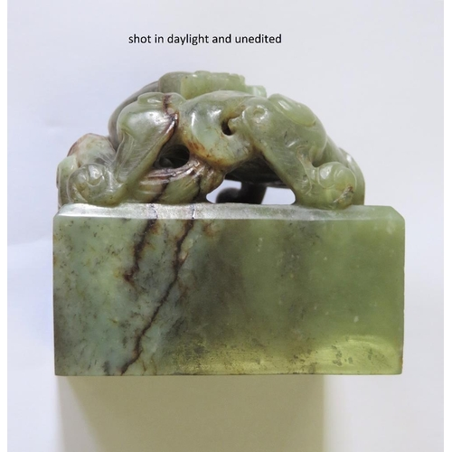 35 - A CHINESE GREEN JADE 'CHILONG' SEAL the straight-sided rectangular seal surmounted by a high relief ...